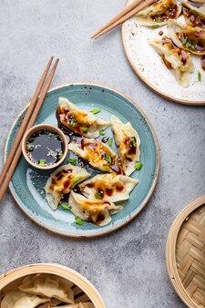 灰色の素朴な石の背景に醤油と箸で伝統的なアジア/中国の餃子と2つのプレートのクローズアップ、上面図。本格的な中華料理