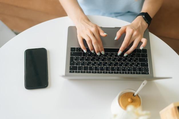 Крупным планом вид сверху неузнаваемой молодой женщины, носящей умные часы, набрав на клавиатуре ноутбука, сидя за столом в кафе с теплым дневным светом. симпатичная дама работает удаленно или учится в помещении.