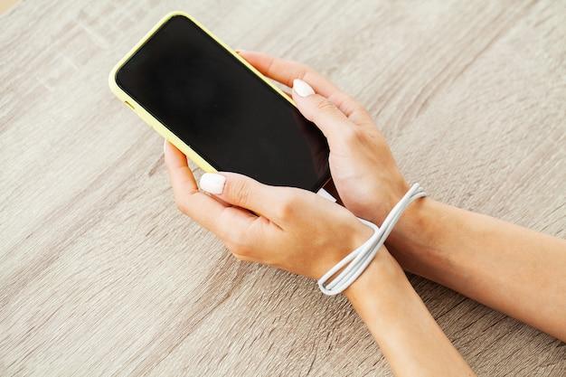 Закройте вверх по взгляду руки женщины, соединенной проводом кабеля к гаджету смартфона.