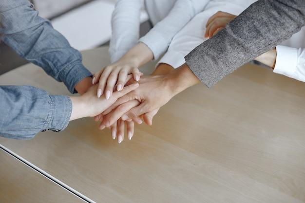 젊은 기업들의 상위 뷰를 닫습니다. 손을 모으는 팀. 손의 스택. 화합과 팀워크 개념.