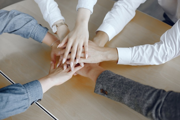 若いビジネスマンの上面図を閉じます。手を合わせてチーム。手のスタック。団結とチームワークの概念。