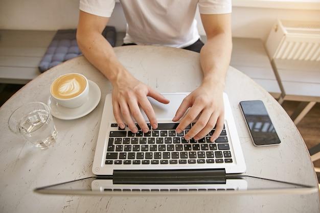 コーヒー、最新のラップトップ、スマートフォンを備えた白いデスクトップのクローズアップ上面図。白いtシャツを着た青年実業家がシティカフェで在宅勤務