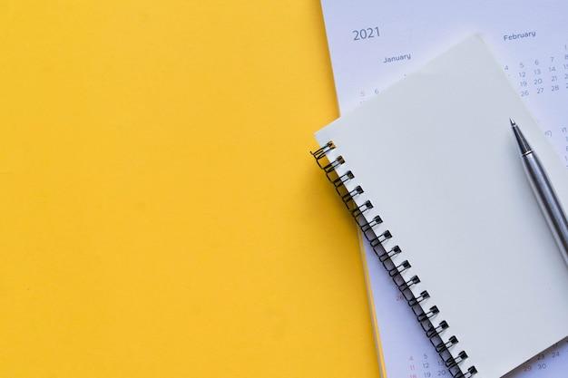 カレンダー2021スケジュールと黄色のペンで空白のノートブックページの上面図を閉じる