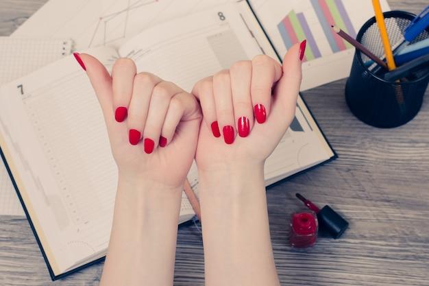 붉은 색으로 칠해진 손톱이 있는 여성의 손의 상단 보기 사진을 닫습니다