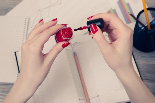 메모장과 문서를 사용하여 테이블 위에 손톱을 칠하는 여성의 손에 대한 상위 뷰 사진을 닫습니다