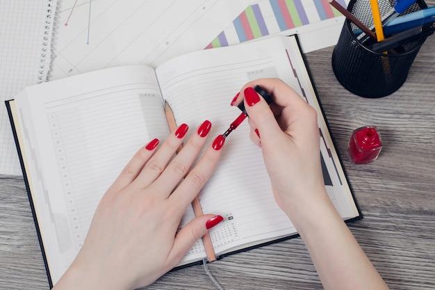 직장에서 손톱을 그리는 여성의 손에 대한 상위 뷰 사진을 닫습니다.
