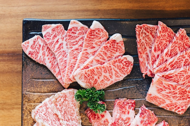 Close-up top view of premium rare slices many parts of wagyu a5 beef with high-marbled texture.