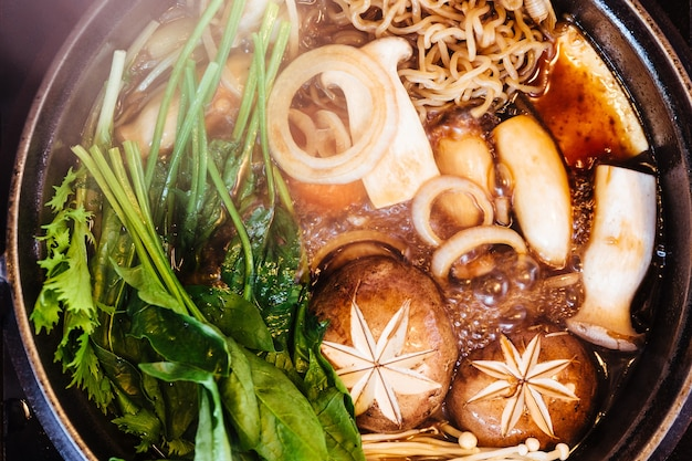 Close up top view of sukiyaki hot pot with boiling vegetables including cabbage, konjac noodle, onion, carrot, shiitake, enokitake and tofu in shoyu sauce soup.