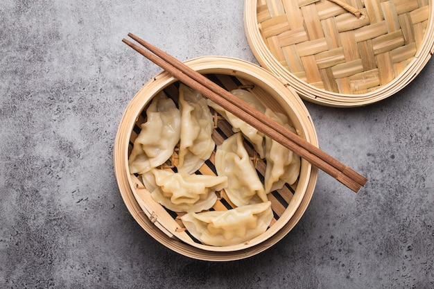 Close-up, top view of traditional asian/chinese dumplings in bamboo steamer with chopsticks on gray rustic stone background. authentic chinese cuisine