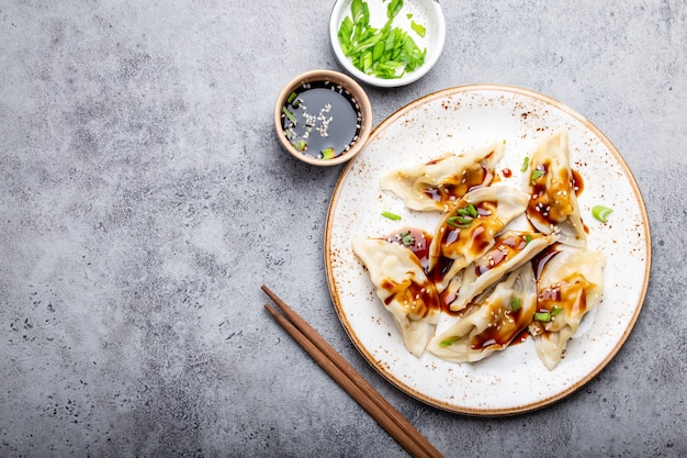 Close-up, top view of traditional asian/chinese dumplings on white plate with soy sauce and chopsticks on gray rustic stone background with space for text. authentic chinese cuisine, copy space