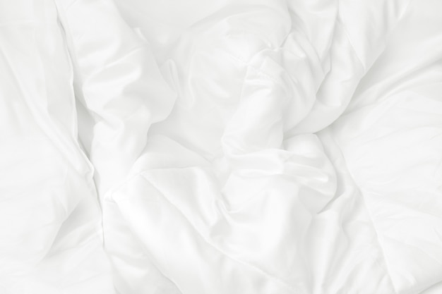 Close up top view of white bedding sheet and wrinkle messy blanket in bedroom.