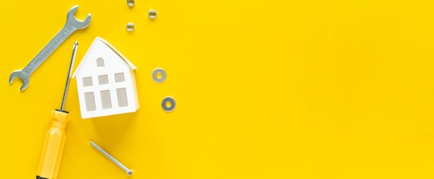 Close up top view on white color of model house with metal wrench and instrument on yellow wallpaper