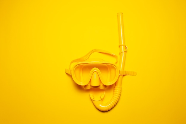 Close-up top view of yellow diving mask with snorkel, isolated on yellow studio background.