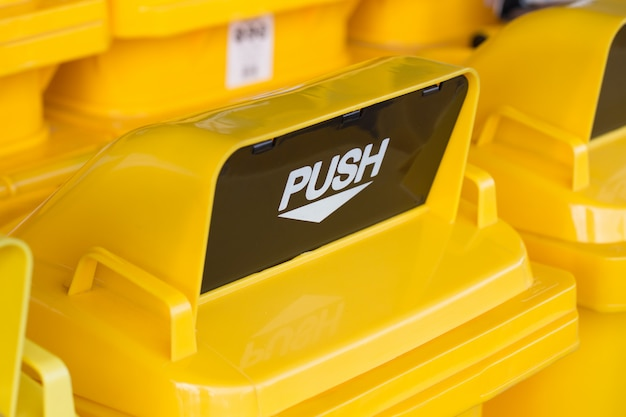 Close up top yellow push hole or waste drop hole of trash bin or recycle bin