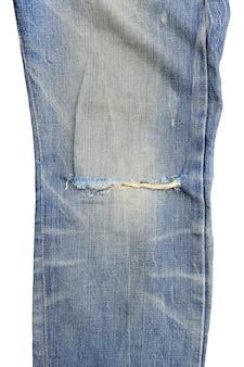 白い背景で隔離のブルージーンズのクローズアップ引き裂かれた。クリッピングパスのあるデニムの服