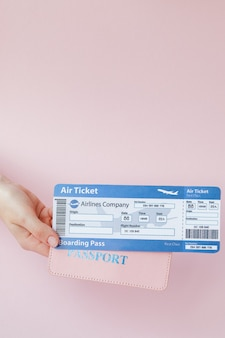 Close up tourist female horizontal hold in hand tickets for plane with orange passport, boarding pass on pink