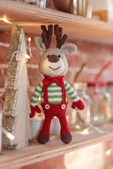 Close up toy amigurumi deer in striped sweater and stylish red butterfly tie stands on the wooden shelf near the decorated christmas tree and christmas lights.