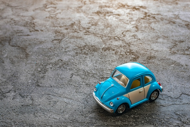 Close up of toy a blue car model on a plaster background