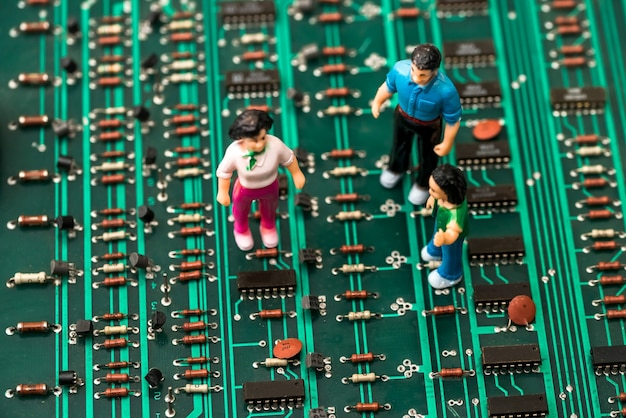 Close up of toy people on green electronic circuit board