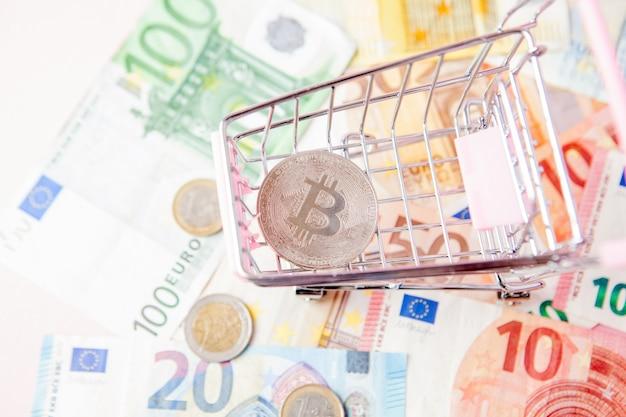 유로 배경에 bitcoin으로 장난감 쇼핑 카트를 닫습니다