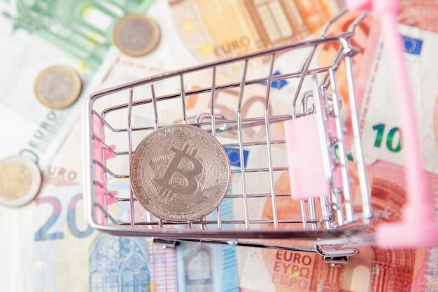 Крупным планом игрушечная тележка с биткойнами на банкнотах евро