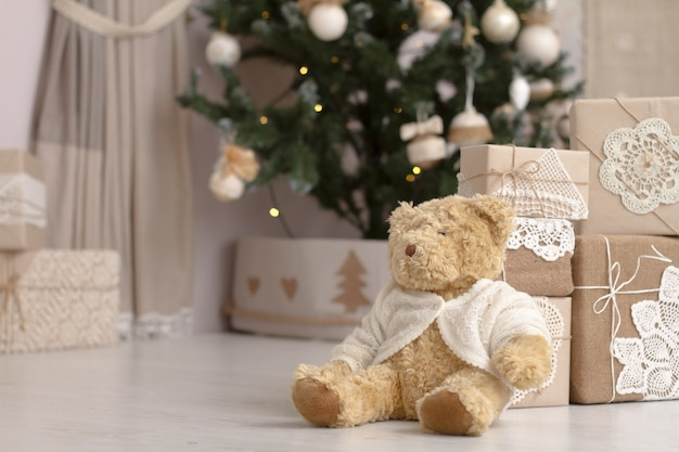 Close-up toy teddy bear near the mountain of gifts packed in craft paper on a blurred background of a decorated christmas tree.