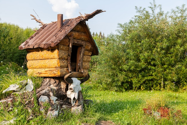 Close-up of a toy wooden house on chicken legs with a skull of an animal buffalo decorations for the garden on a garden stone on a green grass background on a warm summer day.