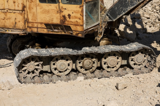 A close-up of the tracks of a heavy large excavator in a mining quarry.