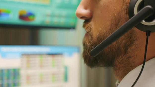 投資家と話しているヘッドフォンを身に着けているトレーダーを閉じます。価格が下がる。