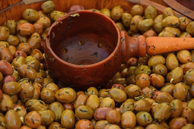 Close up traditional artisanal pickled green olives and natural wooden scoop in a rustic barrel on retail display of open market, high angle view