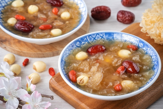 Close up of traditional chinese sweet snow white fungus soup with lotus seed, red dates (jujube) and wolfberry (goji berry, gojiberry) on white background.