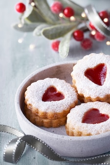 Close-up on traditional christmas linzer jam cookies on white table with xmas decorations