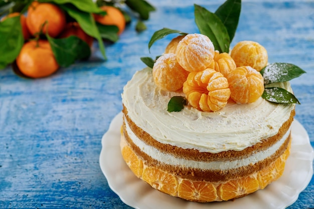 Close up of traditional christmas naked cake with fresh mandarins on blue background.