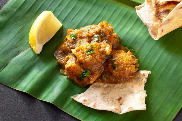 Close up traditional indian butter chicken curry and lemon served with chapati bread on banana leaf.