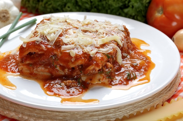 Close-up of a traditional lasagna made with minced beef bolognese sauce topped with basil leafs served on a white plate.