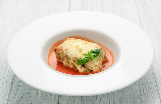 Close-up of a traditional lasagna made with minced beef bolognese sauce topped with basil leafs served