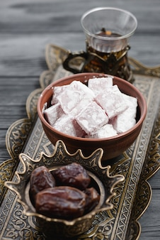 Close-up of traditional turkish delight lukum; dates and tea on metallic tray