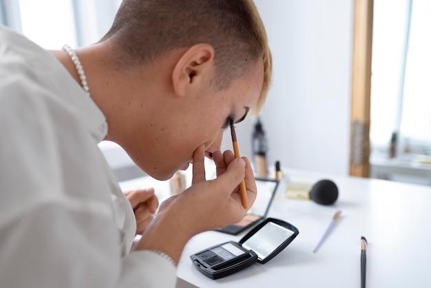 Close up transgender putting on makeup