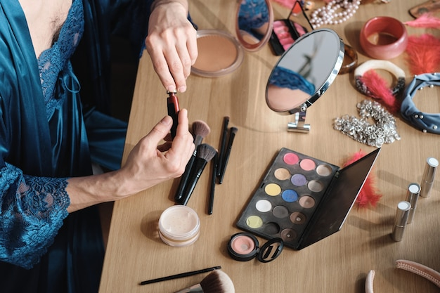 Close-up of transgender sitting at the table using cosmetics for makeup