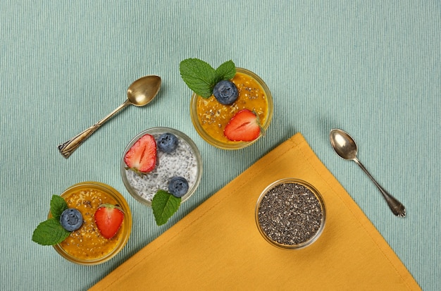 Close up transparent glass jars of chia seeds pudding dessert with coconut milk, mango and fruits served on table, elevated top view, directly above