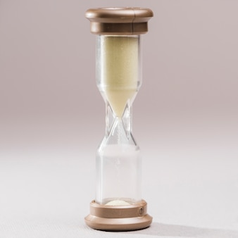 Close-up of a transparent hourglass on colored background