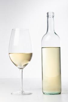 Крупным планом прозрачная бутылка вина и бокал