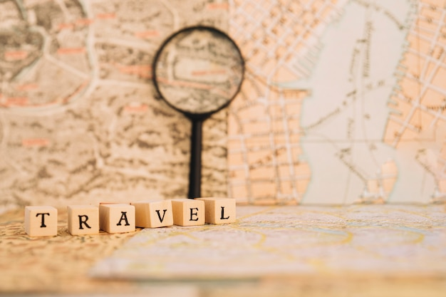 Close-up travel writing near magnifying glass nd maps
