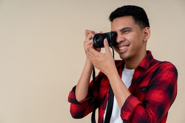Close up traveler hipster man smiling and using mirrorless camera for take photo