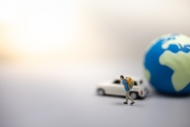 Close up of traveler miniature figure with backpack walking on ground with toy car and world ball.