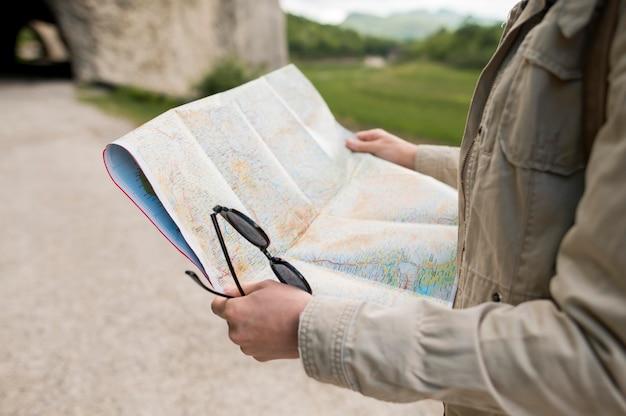 地図とサングラスを保持しているクローズアップの旅行者