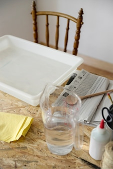 Close-up of a tray and jar filled with water on desk
