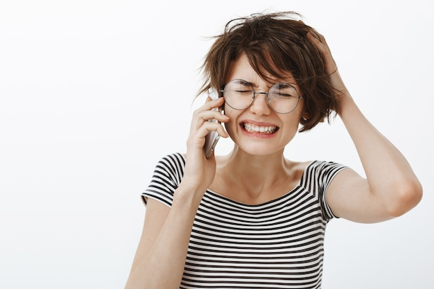 Close-up of troubled and upset woman hear bad news on phone, feeling bothered