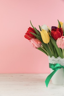 Close-up of tulips in the white vase with green bow on wooden desk against pink background