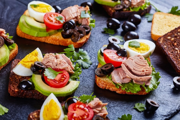 Close-up of tuna sandwiches with avocado slices, lettuce, tomatoes, black olives and hard boiled egg on rye and corn toasted bread slices on a black slate board with ingredients